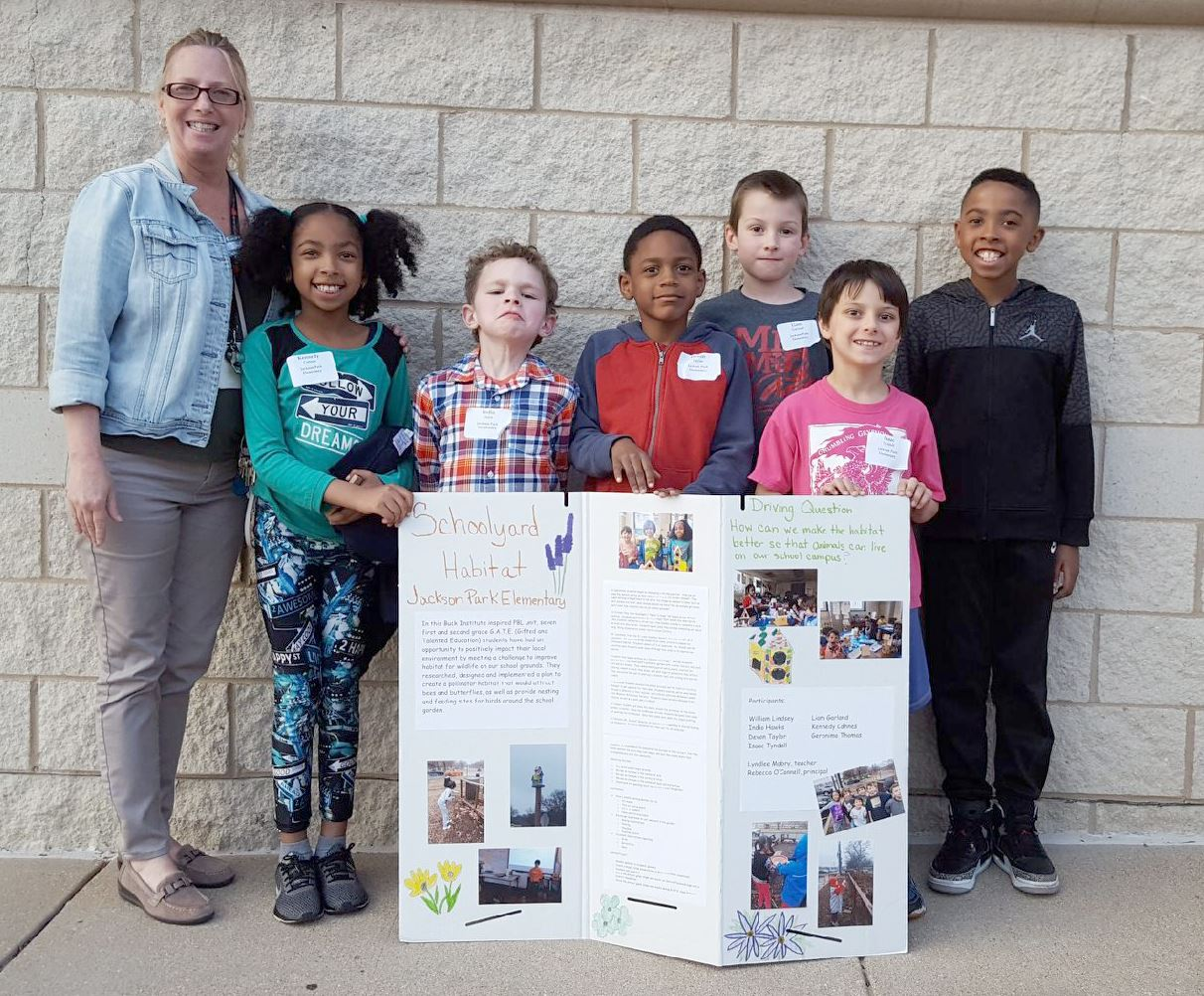 students and teacher with schoolyard habitat project display board