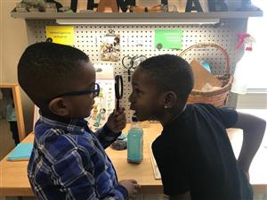 boys looking at each other through magnifying glass