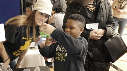 A student interacts with a display table at the 2018 UCity STEM Expo
