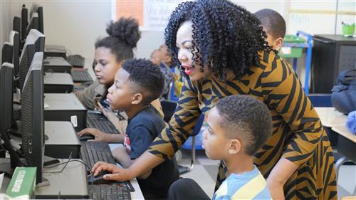 Barbara C. Jordan third-grade teacher Alisha Ashford looks over the shoulder of students