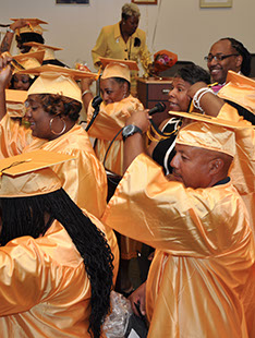 GED Graduates in robes and caps, moving tassles