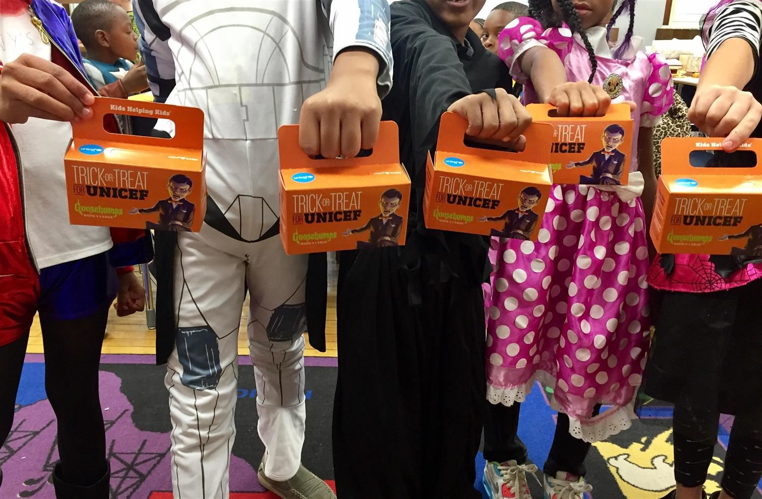 children holding unicef boxes
